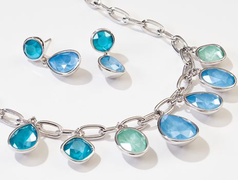 Closeup of Touchstone Crystal Swirling Seas Necklace and Earrings featuring varying tones of blue and sea foam green